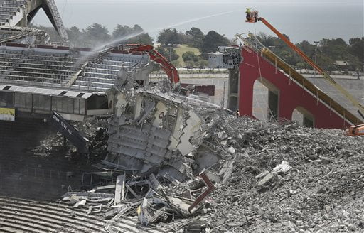 Worker spray water on a collapsed section of seating as demolition continues at Candlestick Park Tuesday, May 5, 2015, in San Francisco. The storied park is being torn down so houses, a hotel and a shopping center can be built on the site of the former home of the San Francisco Giants baseball team and 49ers football team. The park opened more than 50 years ago and was known for its chilly conditions brought by whipping winds and fog from San Francisco Bay. (AP Photo/Eric Risberg)