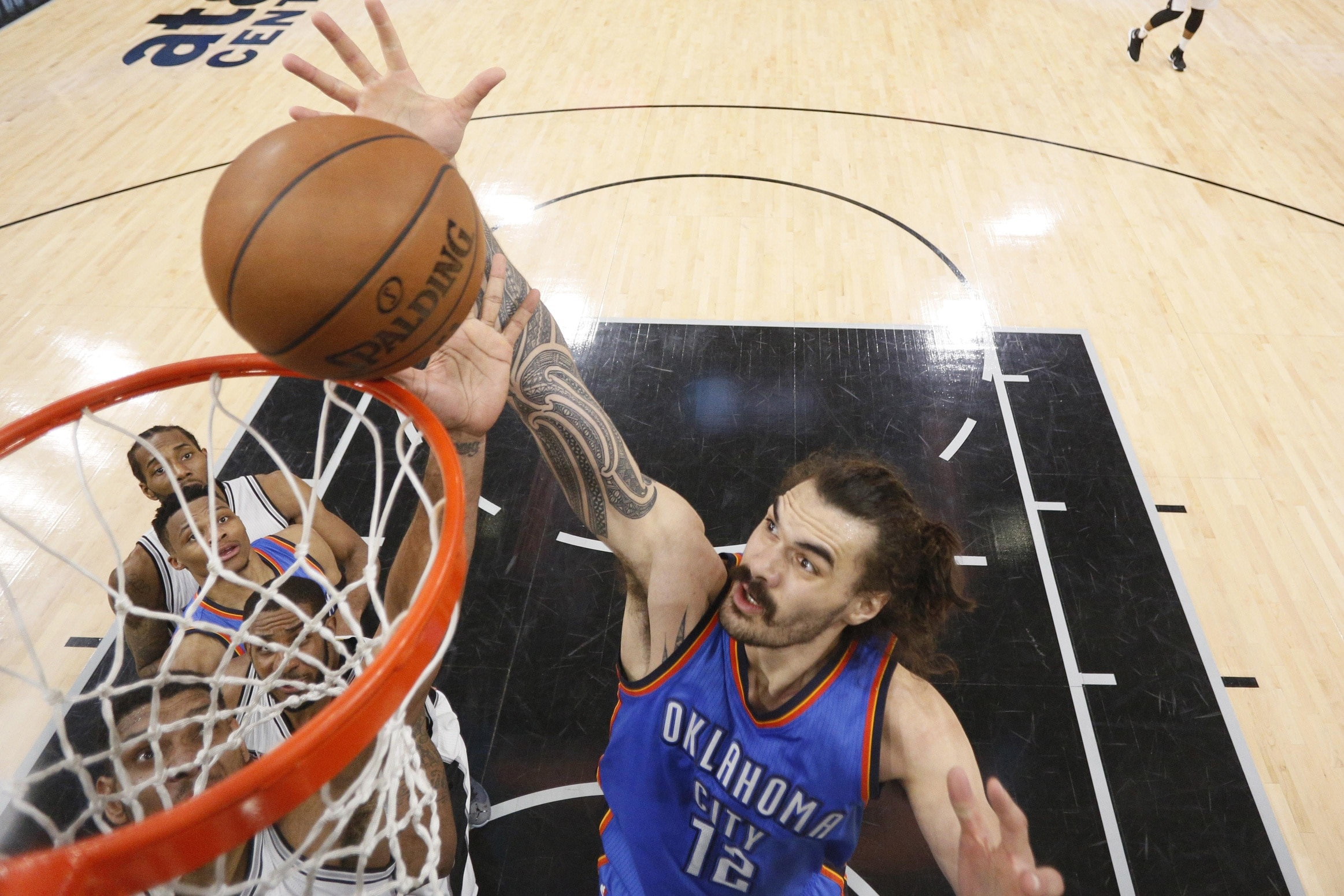 May 10, 2016; San Antonio, TX, USA; Oklahoma City Thunder center Steven Adams (12) and San Antonio Spurs power forward Tim Duncan (21, left) go for a rebound in game five of the second round of the NBA Playoffs at AT&T Center. Mandatory Credit: Soobum Im-USA TODAY Sports