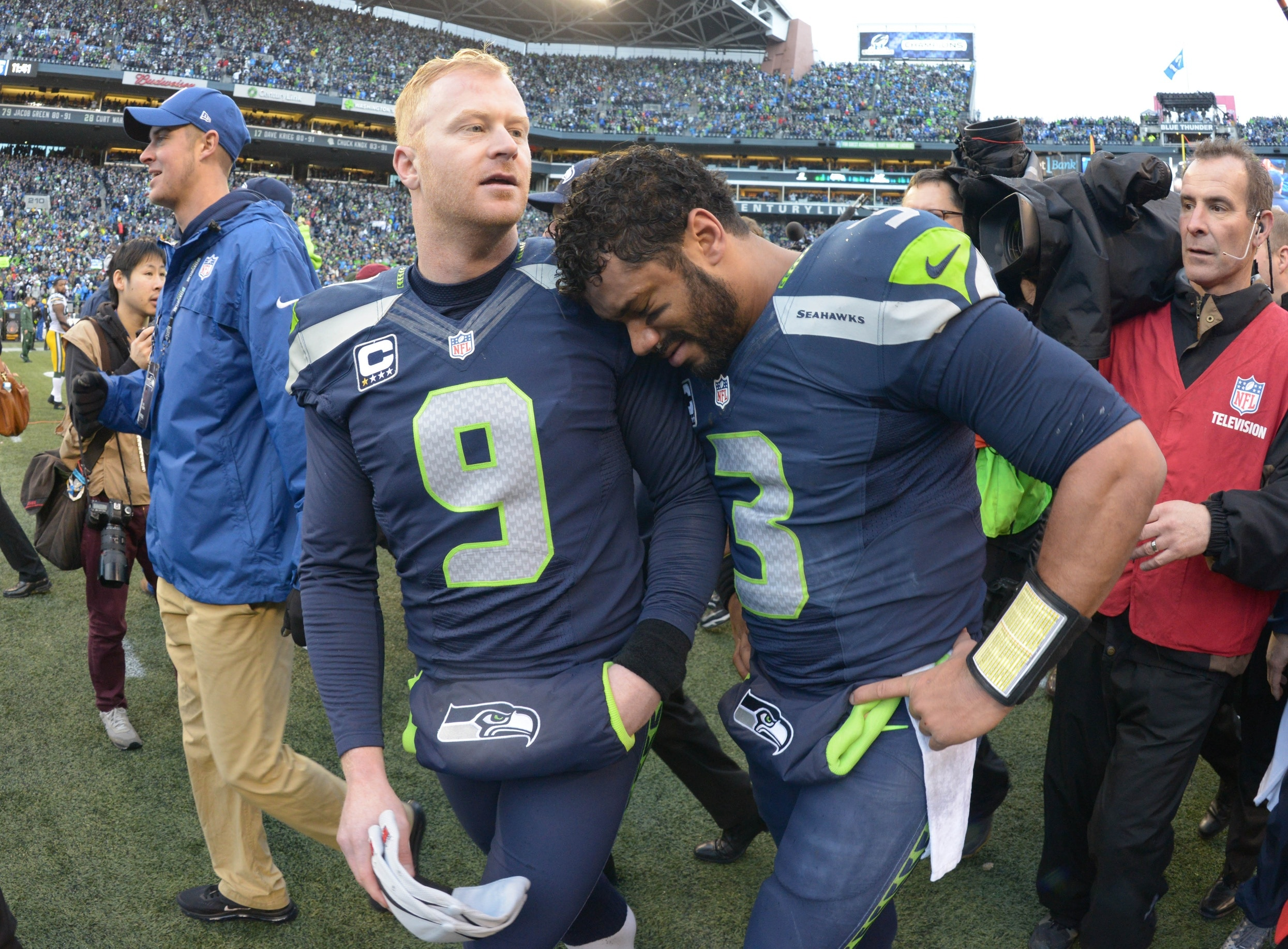 Jan 18, 2015; Seattle, WA, USA; Seattle Seahawks punter Jon Ryan (9) and Russell Wilson (3) celebrate following the overtime victory over the Green Bay Packers in the NFC Championship Game at CenturyLink Field. The Seahawks defeated the Packers 28-22 in overtime. Mandatory Credit: Kirby Lee-USA TODAY Sports
