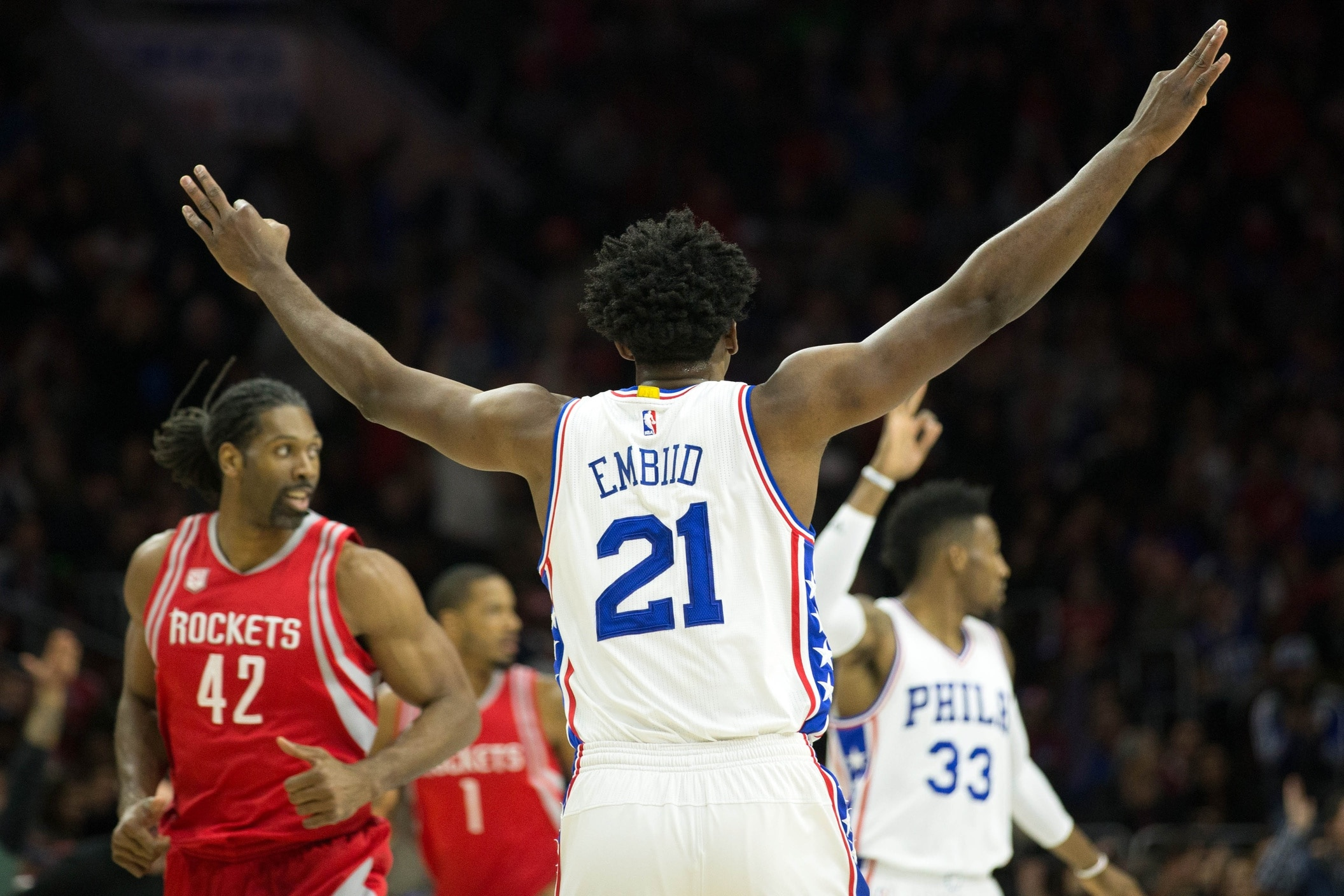 Jan 27, 2017; Philadelphia, PA, USA; Philadelphia 76ers center Joel Embiid (21) reacts to his three pointer in front of Houston Rockets center Nene Hilario (42) during the first quarter at Wells Fargo Center. Mandatory Credit: Bill Streicher-USA TODAY Sports