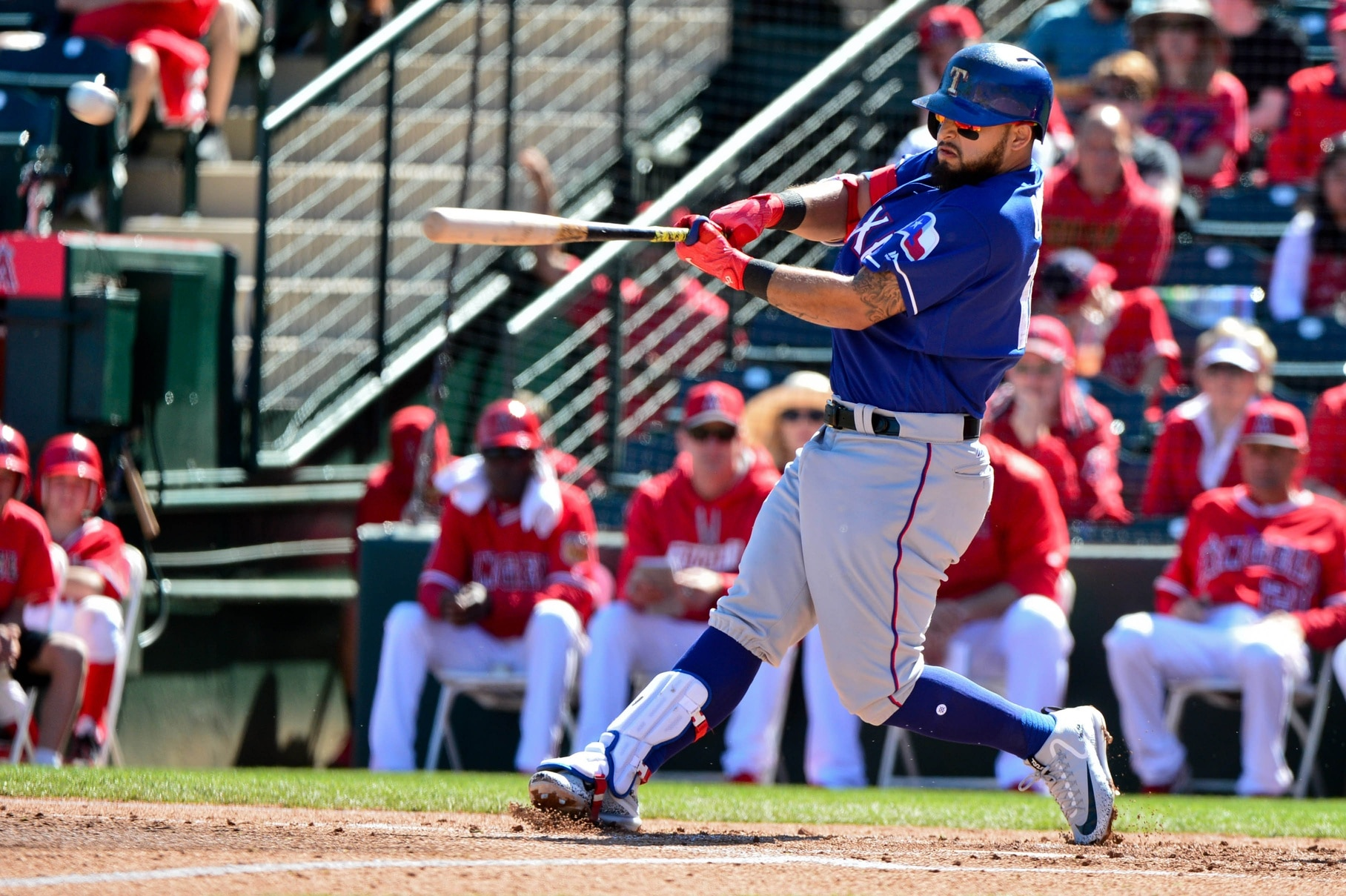Caption: Mar 23, 2017; Surprise, AZ, USA; Texas Rangers second baseman Rougned Odor (12) runs to first with his bat as he flew out during the fourth inning against the Los Angeles Dodgers at Surprise Stadium. Mandatory Credit: Jake Roth-USA TODAY Sports