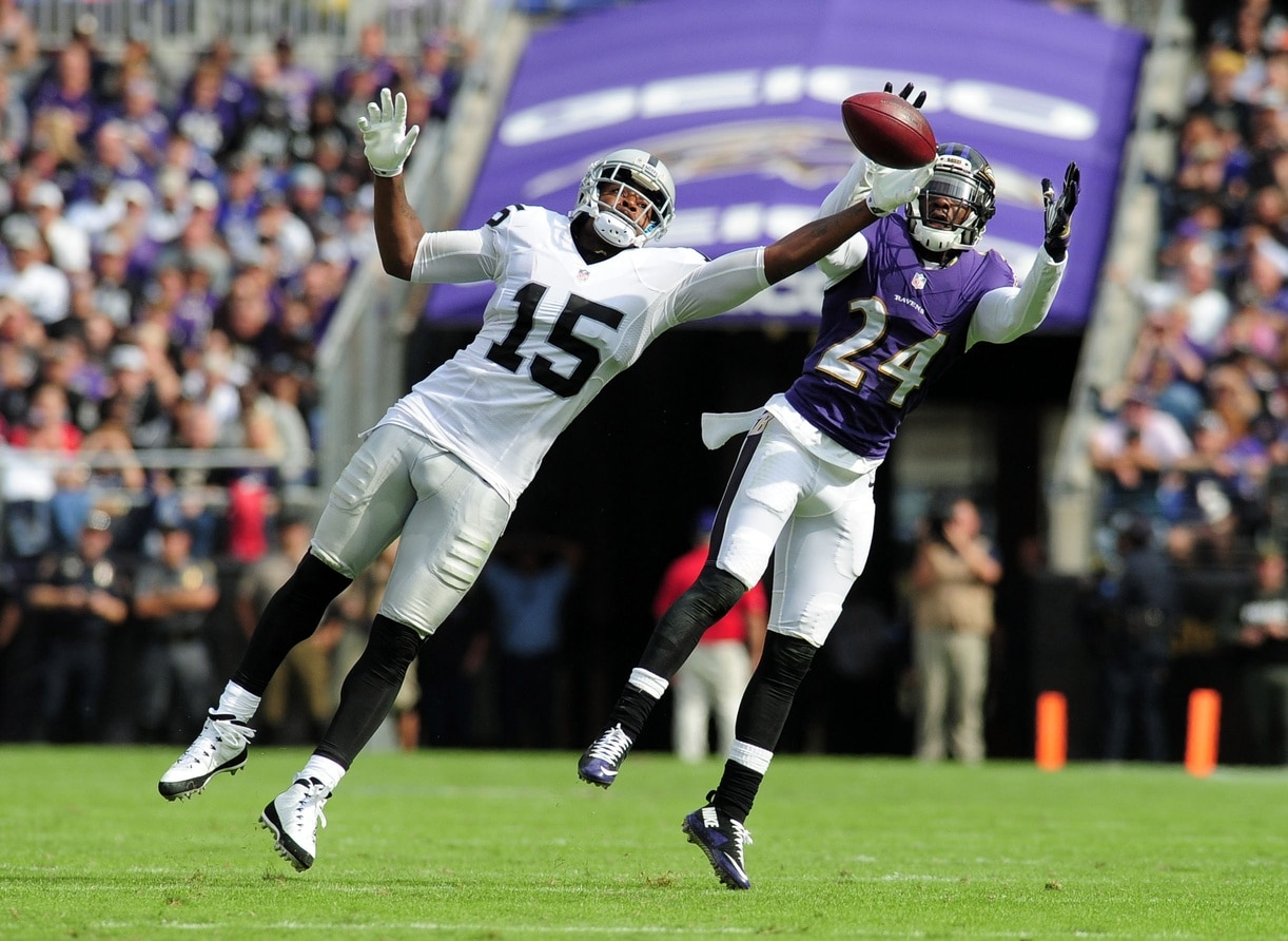 Michael Crabtree and Shareece Wright battle for a ball