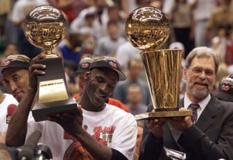 Michael Jordan holds the MVP trophy and coach Phil Jackson holds the championship trophy after the Bulls beat the Jazz to win their sixth title in 1998