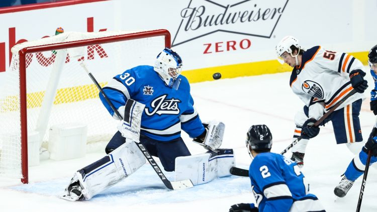 Jan 24, 2021; Winnipeg, Manitoba, CAN;  Winnipeg Jets goalie Laurent Brossoit (30) makes a save with Edmonton Oilers forward Kailer Yamamoto (56) looking for a rebound during the second period at Bell MTS Place. Mandatory Credit: Terrence Lee-USA TODAY Sports