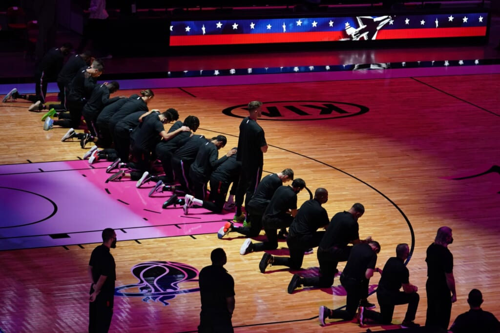 Heat and Celtics players kneel during the national anthem.