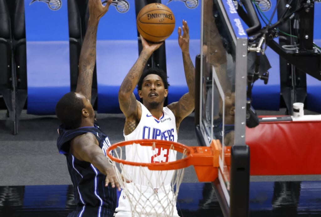 Jan 29, 2021; Orlando, Florida, USA;  LA Clippers guard Lou Williams (23) shoots over Orlando Magic forward James Ennis III (11) during the first quarter at Amway Center. Mandatory Credit: Reinhold Matay-USA TODAY Sports