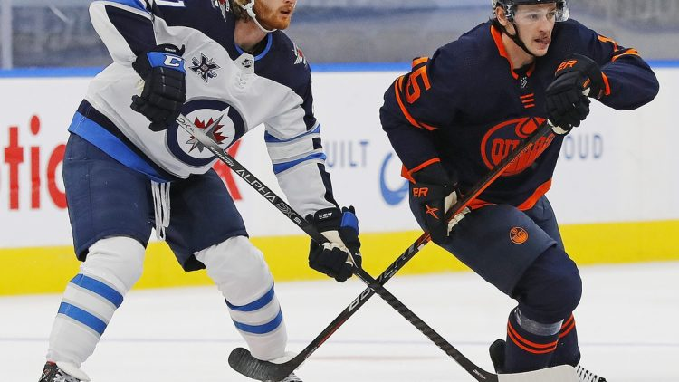 Feb 17, 2021; Edmonton, Alberta, CAN; Winnipeg Jets forward Kyle Connor (81) and Edmonton Oilers forward Josh Archibald (15) look for a loose puck during the first period at Rogers Place. Mandatory Credit: Perry Nelson-USA TODAY Sports
