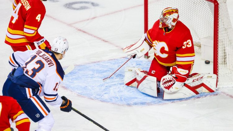 Feb 19, 2021; Calgary, Alberta, CAN; Calgary Flames goaltender David Rittich (33) reacts as Edmonton Oilers right wing Jesse Puljujarvi (13) scores a goal during the first period at Scotiabank Saddledome. Mandatory Credit: Sergei Belski-USA TODAY Sports