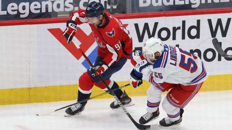 Feb 20, 2021; Washington, District of Columbia, USA; Washington Capitals center Evgeny Kuznetsov (92). Skates with the puck as New York Rangers defenseman Ryan Lindgren (55) defends in the first period at Capital One Arena. Mandatory Credit: Geoff Burke-USA TODAY Sports