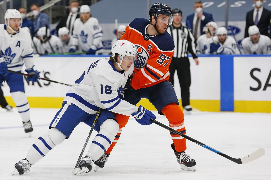 Feb 27, 2021; Edmonton, Alberta, CAN; Toronto Maple Leafs forward Mitch Marner (16) and Edmonton Oilers forward Connor McDavid (97) battle for position during the second period at Rogers Place. Mandatory Credit: Perry Nelson-USA TODAY Sports