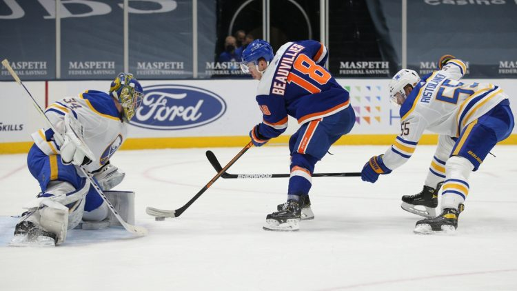 Mar 4, 2021; Uniondale, New York, USA; New York Islanders left wing Anthony Beauvillier (18) scores a goal against Buffalo Sabres goalie Jonas Johansson (34) in front of Sabres defenseman Rasmus Ristolainen (55) during the second period at Nassau Veterans Memorial Coliseum. Mandatory Credit: Brad Penner-USA TODAY Sports