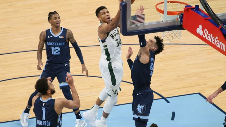 Mar 4, 2021; Memphis, Tennessee, USA; Milwaukee Bucks forward Giannis Antetokounmpo (34) shoots as Memphis Grizzlies  guard Dillon Brooks (24) defends while guard Ja Morant (12) looks on in the second quarter at FedExForum. Mandatory Credit: Nelson Chenault-USA TODAY Sports