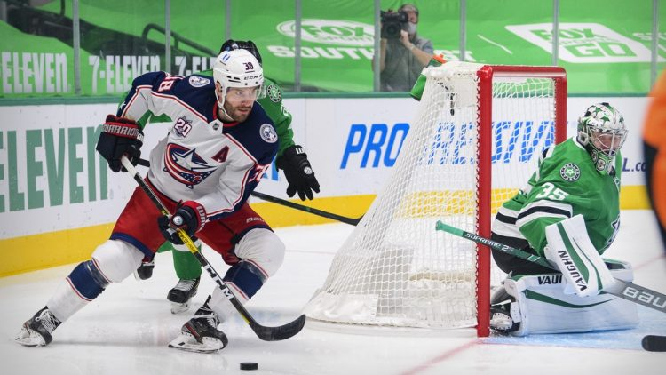 Mar 4, 2021; Dallas, Texas, USA; Columbus Blue Jackets center Boone Jenner (38) skates against the Stars as Dallas Stars goaltender Anton Khudobin (35) defends the goal during the first period at the American Airlines Center. Mandatory Credit: Jerome Miron-USA TODAY Sports