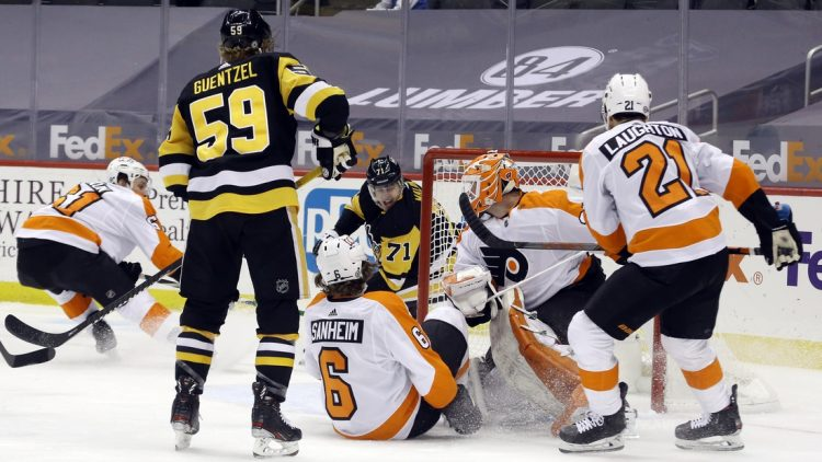 Mar 6, 2021; Pittsburgh, Pennsylvania, USA; Pittsburgh Penguins center Evgeni Malkin (71) scores a goal on a wrap around shot against Philadelphia Flyers goaltender Brian Elliott (37) during the first period at PPG Paints Arena. Mandatory Credit: Charles LeClaire-USA TODAY Sports