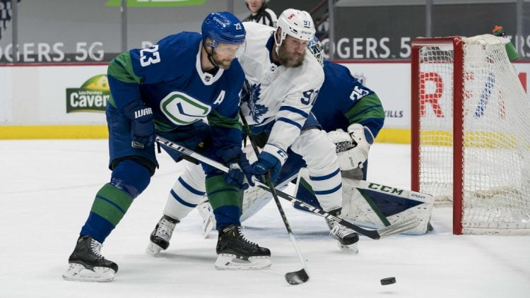 Mar 6, 2021; Vancouver, British Columbia, CAN; Vancouver Canucks defenseman Alexander Edler (23) checks Toronto Maple Leafs forward  Joe Thornton (97) in the first period at Rogers Arena. Mandatory Credit: Bob Frid-USA TODAY Sports