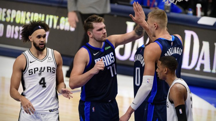 Mar 10, 2021; Dallas, Texas, USA; Dallas Mavericks guard Luka Doncic (77) and center Kristaps Porzingis (6) celebrate as San Antonio Spurs guard Derrick White (4) looks on during the second half at the American Airlines Center. Mandatory Credit: Jerome Miron-USA TODAY Sports