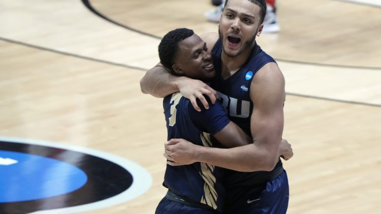 Mar 19, 2021; West Lafayette, Indiana, USA; Oral Roberts Golden Eagles guard Max Abmas (3) and forward Kevin Obanor (0) celebrate after an overtime victory over the Ohio State Buckeyes in the first round of the 2021 NCAA Tournament at Mackey Arena. Mandatory Credit: Mike Dinovo-USA TODAY Sports