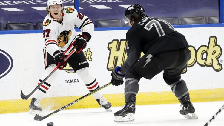 Mar 20, 2021; Tampa, Florida, USA; Chicago Blackhawks defenseman Adam Boqvist (27) passes the puck as Tampa Bay Lightning center Anthony Cirelli (71) defends during the second period at Amalie Arena. Mandatory Credit: Kim Klement-USA TODAY Sports