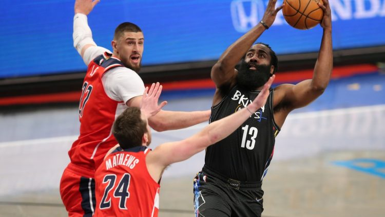 Mar 21, 2021; Brooklyn, New York, USA; Brooklyn Nets shooting guard James Harden (13) drives to the basket against Washington Wizards center Alex Len (27) and small forward Garrison Mathews (24) during the first quarter at Barclays Center. Mandatory Credit: Brad Penner-USA TODAY Sports