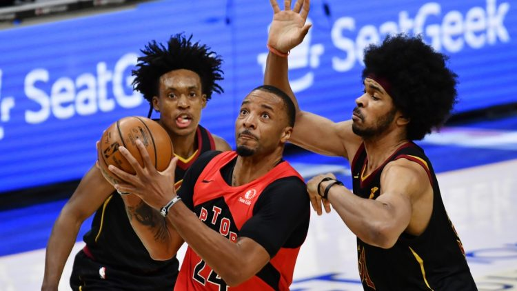 Mar 21, 2021; Cleveland, Ohio, USA; Toronto Raptors forward Norman Powell (24) drives to the basket between Cleveland Cavaliers guard Collin Sexton (2) and center Jarrett Allen (31) during the third quarter at Rocket Mortgage FieldHouse. Mandatory Credit: Ken Blaze-USA TODAY Sports