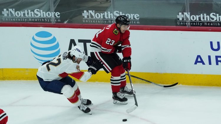 Mar 23, 2021; Chicago, Illinois, USA; Florida Panthers defenseman MacKenzie Weegar (52) and Chicago Blackhawks left wing Philipp Kurashev (23) go for the puck during the first period at United Center. Mandatory Credit: David Banks-USA TODAY Sports