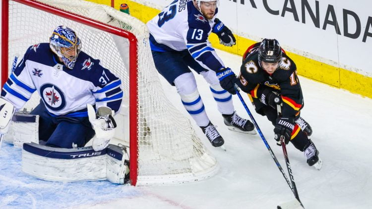 Mar 26, 2021; Calgary, Alberta, CAN; Winnipeg Jets goaltender Connor Hellebuyck (37) guards his net as Calgary Flames left wing Johnny Gaudreau (13) and Winnipeg Jets center Pierre-Luc Dubois (13) battle for the puck during the second period at Scotiabank Saddledome. Mandatory Credit: Sergei Belski-USA TODAY Sports