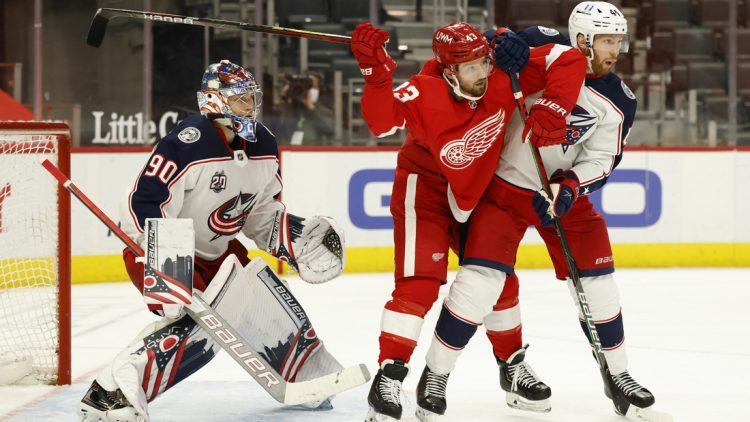 Mar 27, 2021; Detroit, Michigan, USA;  Detroit Red Wings left wing Darren Helm (43) and Columbus Blue Jackets defenseman Vladislav Gavrikov (44) fight for position with in front of goaltender Elvis Merzlikins (90) in the second period at Little Caesars Arena. Mandatory Credit: Rick Osentoski-USA TODAY Sports