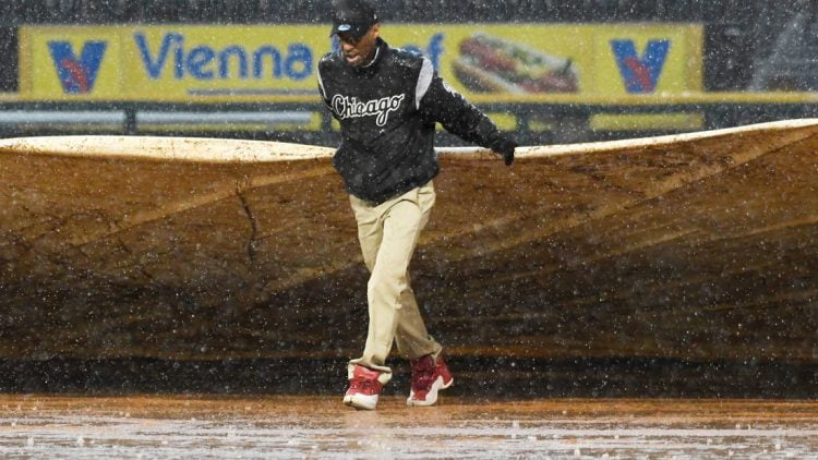 May 27, 2019; Chicago, IL, USA; A member of the grounds crew helps put a tarp on the field in a rain delay during the fifth inning of a game between the Chicago White Sox and the Kansas City Royals at Guaranteed Rate Field. Mandatory Credit: David Banks-USA TODAY Sports
