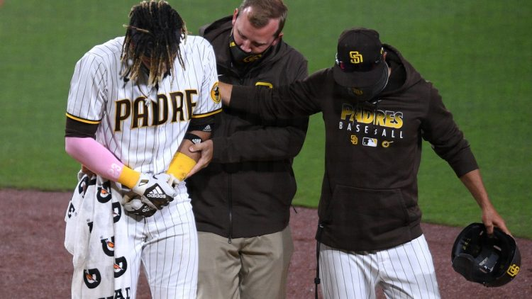 Apr 5, 2021; San Diego, California, USA; San Diego Padres shortstop Fernando Tatis Jr. (L) is helped off the field by a trainer and manager Jayce Tingler (R) after injuring himself during a swing during the third inning against the San Francisco Giants at Petco Park. Mandatory Credit: Orlando Ramirez-USA TODAY Sports