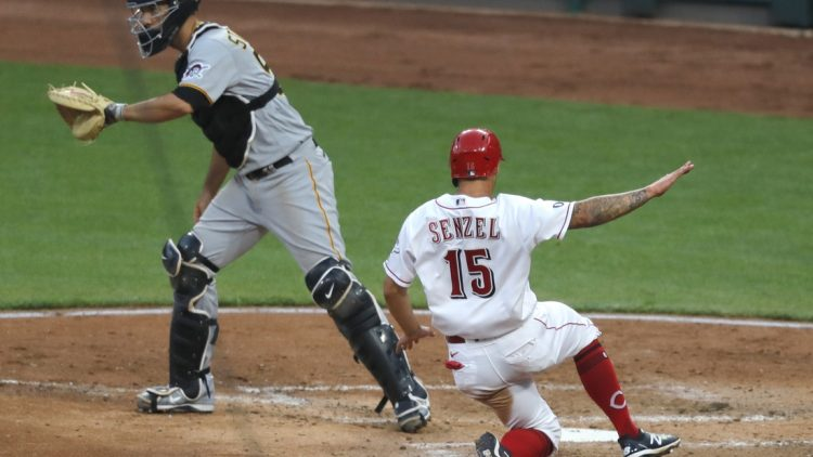 Apr 6, 2021; Cincinnati, Ohio, USA; Cincinnati Reds center fielder Nick Senzel (15) scores against Pittsburgh Pirates catcher Jacob Stallings (58) during the fourth inning at Great American Ball Park. Mandatory Credit: David Kohl-USA TODAY Sports