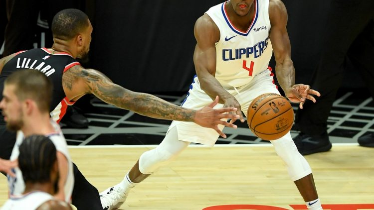 Apr 6, 2021; Los Angeles, California, USA; Los Angeles Clippers guard Rajon Rondo (4) is defended by Portland Trail Blazers guard Damian Lillard (0)as he passes the ball in the first half of the game at Staples Center. Mandatory Credit: Jayne Kamin-Oncea-USA TODAY Sports