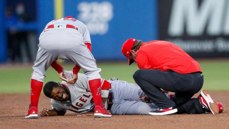 Apr 9, 2021; Dunedin, Florida, CAN; Los Angeles Angels right fielder Dexter Fowler (25) is attended to by manager Joe Maddon (left) after injuring his knee on a slide into second base in a game against the Toronto Blue Jays t TD Ballpark. Mandatory Credit: Nathan Ray Seebeck-USA TODAY Sports
