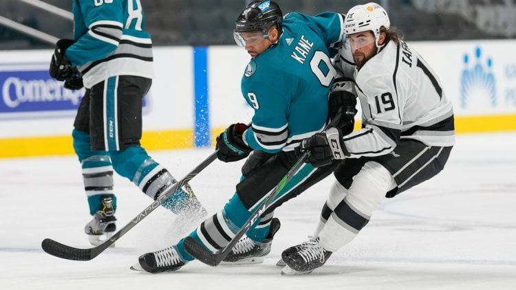 Apr 9, 2021; San Jose, California, USA; San Jose Sharks left wing Evander Kane (9) and Los Angeles Kings right wing Alex Iafallo (19) chase after the puck during the first period at SAP Center at San Jose. Mandatory Credit: Stan Szeto-USA TODAY Sports