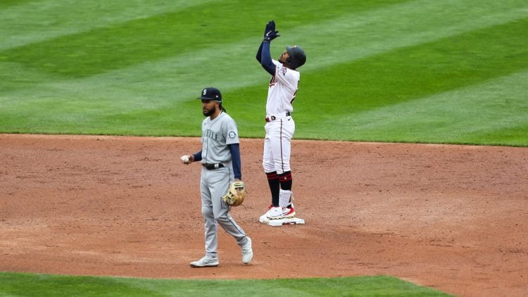 Apr 11, 2021; Minneapolis, Minnesota, USA; Minnesota Twins center fielder Byron Buxton (25) celebrates after hitting an RBI double in the third inning while Seattle Mariners shortstop J.P. Crawford (3) looks on at Target Field. Mandatory Credit: David Berding-USA TODAY Sports