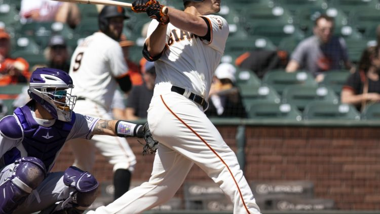 Apr 11, 2021; San Francisco, California, USA; San Francisco Giants batter Alex Dickerson (12) follows through on his solo home run again the Colorado Rockies during the first inning of a Major League Baseball game at Oracle Park. Mandatory Credit: D. Ross Cameron-USA TODAY Sports