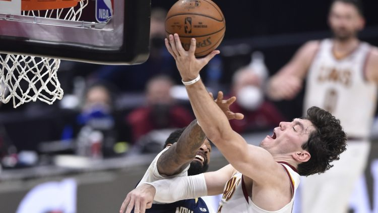 Apr 11, 2021; Cleveland, Ohio, USA; Cleveland Cavaliers forward Cedi Osman (16) goes to the basket while defended by New Orleans Pelicans forward James Johnson (16) during the second quarter at Rocket Mortgage FieldHouse. Mandatory Credit: David Richard-USA TODAY Sports
