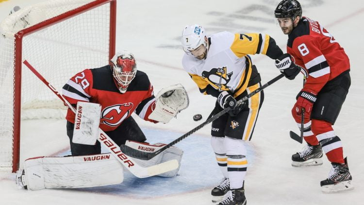 Apr 11, 2021; Newark, New Jersey, USA; Pittsburgh Penguins center Colton Sceviour (7) deflects a shot in front of New Jersey Devils goaltender Mackenzie Blackwood (29) and defenseman Will Butcher (8) during the second period at Prudential Center. Mandatory Credit: Vincent Carchietta-USA TODAY Sports