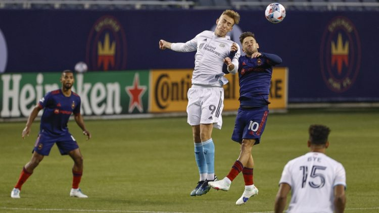 Apr 17, 2021; Chicago, Illinois, USA; New England Revolution forward Adam Buksa (9) battles for the ball with Chicago Fire midfielder Alvaro Medran (10) during the first half at Soldier Field. Mandatory Credit: Kamil Krzaczynski-USA TODAY Sports