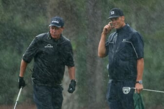 May 24, 2020; Hobe Sound, FL, USA; Phil Mickelson and NFL player Tom Brady of the Tampa Bay Buccaneers react on the 13th green in the rain during The Match: Champions for Charity golf round at the Medalist Golf Club.  Mandatory Credit: Handout Photo by Getty Images for The Match via USA TODAY Sports