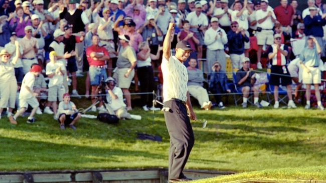 Tiger Woods reacts to the crowd on on the walkway from the green while waiting for playing partner Phil Mickelson to putt in after after Woods sunk a 60-foot birdie putt at the 17th hole of the TPC Sawgrass Players Stadium Course on March 24, 2001, in the third round of The Players Championship. Woods went on to win the tournament two days later in a Monday finish. [Bob Self/Florida Times-Union]  Tiger Putt Reaction