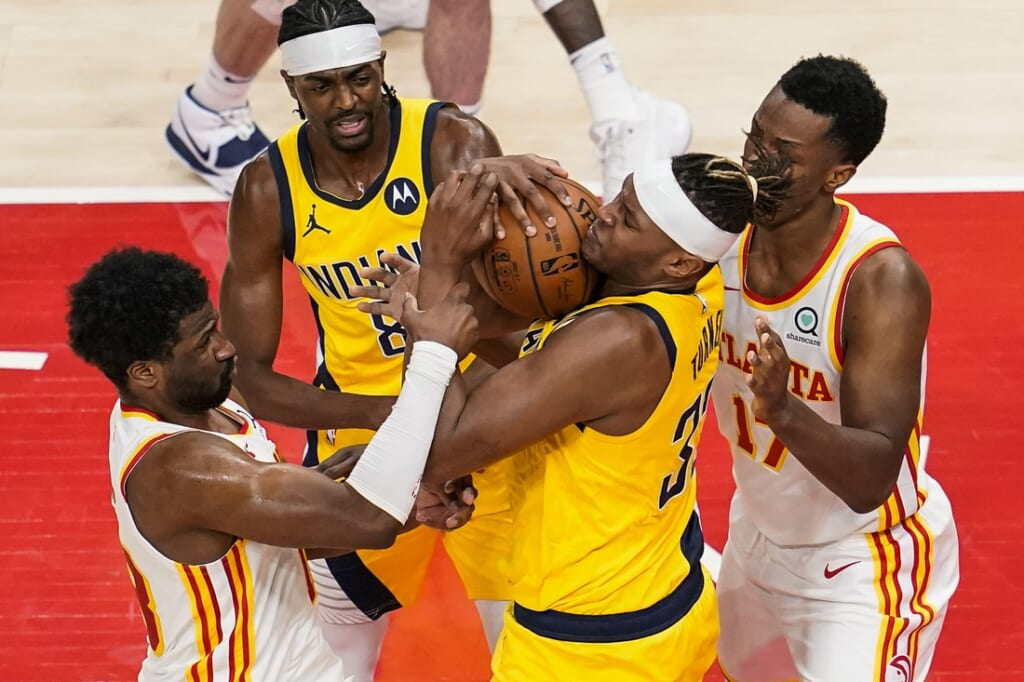 Apr 18, 2021; Atlanta, Georgia, USA; Indiana Pacers center Myles Turner (33) fights for the ball with Atlanta Hawks forward Solomon Hill (18) (left) and forward Onyeka Okongwu (17) during the second half at State Farm Arena. Mandatory Credit: Dale Zanine-USA TODAY Sports