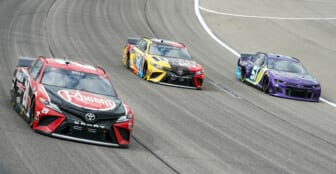 May 2, 2021; Kansas City, Kansas, USA; NASCAR Cup Series driver Kyle Busch (18) races against driver Christopher Bell (20) and driver Cody Ware (51) during the Buschy McBusch Race 400 at Kansas Speedway. Mandatory Credit: Jay Biggerstaff-USA TODAY Sports