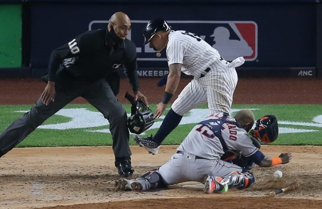 May 4, 2021; Bronx, New York, USA; New York Yankees second baseman Rougned Odor (18) collides with Houston Astros catcher Martin Maldonado (15) while scoring on a hit by Yankees first baseman DJ LeMahieu (not pictured) during the sixth inning at Yankee Stadium. Mandatory Credit: Brad Penner-USA TODAY Sports
