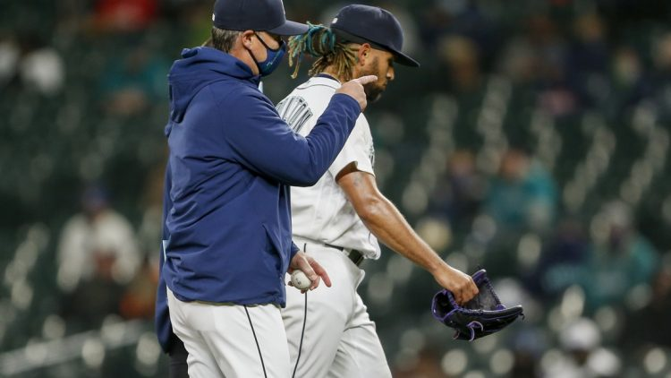 May 4, 2021; Seattle, Washington, USA; Seattle Mariners manager Scott Servais (left) signals for a new pitcher as relief pitcher Keynan Middleton (99) leaves the mound after suffering an injury during the ninth inning against the Baltimore Orioles at T-Mobile Park. Mandatory Credit: Joe Nicholson-USA TODAY Sports