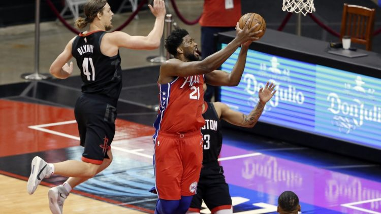 May 5, 2021; Houston, Texas, USA;  Philadelphia 76ers center Joel Embiid (21) gets a shot up past Houston Rockets forward Kelly Olynyk (41) and guard Kevin Porter Jr., right, during the second half at Toyota Center. Mandatory Credit:  Michael Wyke/POOL PHOTOS-USA TODAY Sports