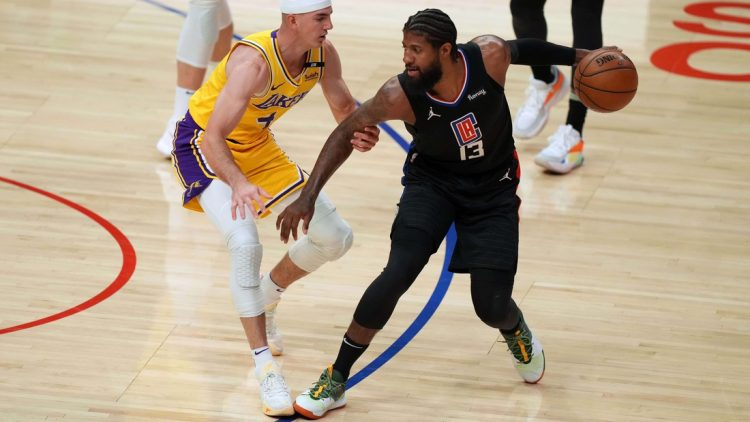 May 6, 2021; Los Angeles, California, USA; LA Clippers guard Paul George (13) handles the ball while defended by Los Angeles Lakers guard Alex Caruso (4) in the first half at Staples Center. Mandatory Credit: Kirby Lee-USA TODAY Sports