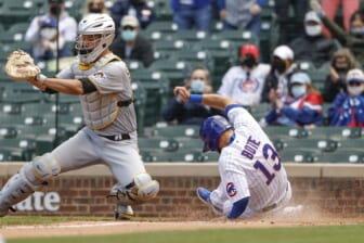 May 7, 2021; Chicago, Illinois, USA; Chicago Cubs second baseman David Bote (13) scores as Pittsburgh Pirates catcher Jacob Stallings (58) waits for the ball during the second inning at Wrigley Field. Mandatory Credit: Kamil Krzaczynski-USA TODAY Sports
