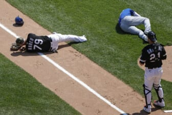 May 14, 2021; Chicago, Illinois, USA; Chicago White Sox first baseman Jose Abreu (79) and Kansas City Royals third baseman Hunter Dozier (17) lay on the field after colliding along the first base line during the second inning of the first game of a doubleheader at Guaranteed Rate Field. Mandatory Credit: Kamil Krzaczynski-USA TODAY Sports