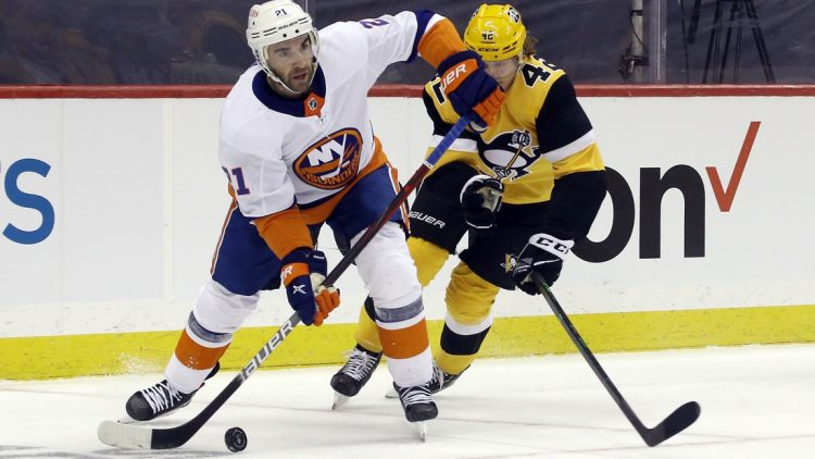 May 16, 2021; Pittsburgh, Pennsylvania, USA; New York Islanders right wing Kyle Palmieri (21) moves the puck against Pittsburgh Penguins right wing Kasperi Kapanen (42) during the first period in game one of the first round of the 2021 Stanley Cup Playoffs at PPG Paints Arena. Mandatory Credit: Charles LeClaire-USA TODAY Sports