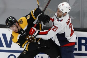 May 19, 2021; Boston, Massachusetts, USA; Washington Capitals right wing Garnet Hathaway (21) checks Boston Bruins defenseman Mike Reilly (6) during the first period in game three of the first round of the 2021 Stanley Cup Playoffs at TD Garden. Mandatory Credit: Winslow Townson-USA TODAY Sports